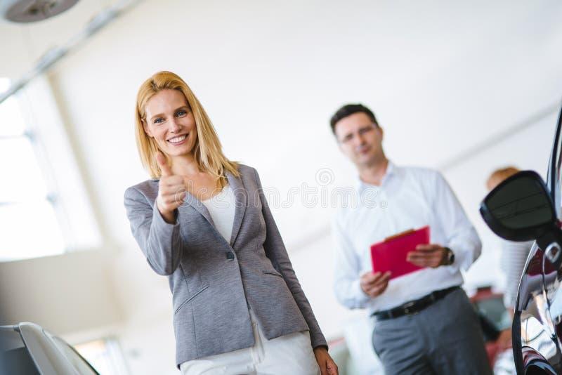 Consultor femenino joven de las ventas del coche que trabaja en la sala de exposici?n foto de archivo libre de regalías