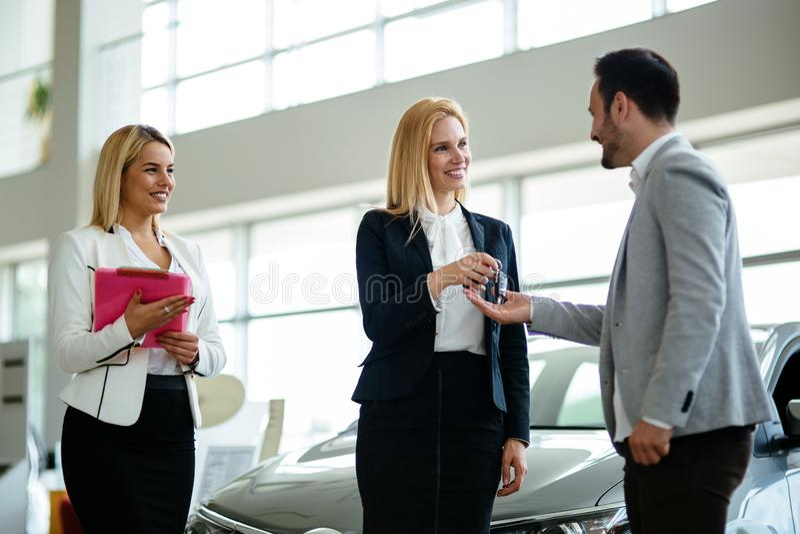 Consultor femenino joven de las ventas del coche que trabaja en la sala de exposici?n fotografía de archivo