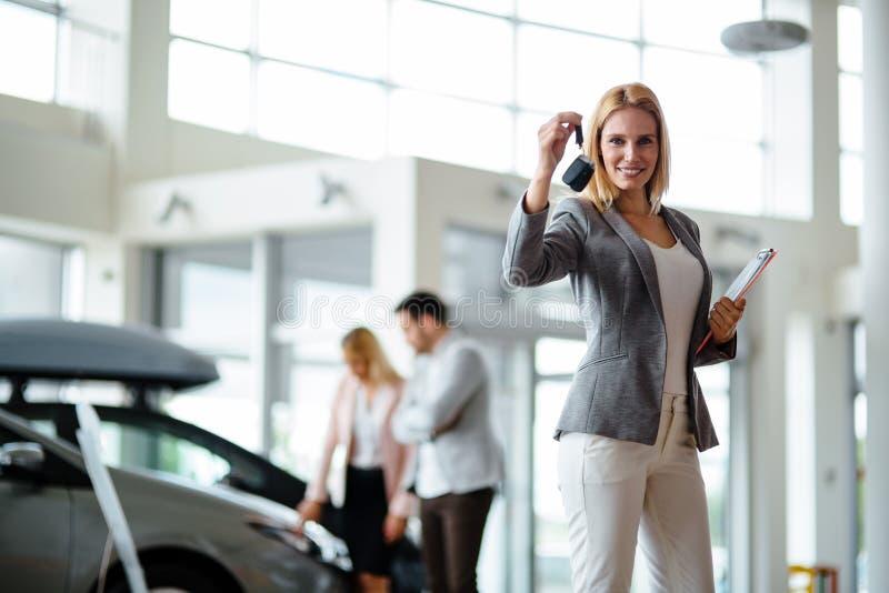 Consultor femenino joven de las ventas del coche que trabaja en la sala de exposici?n imagen de archivo libre de regalías