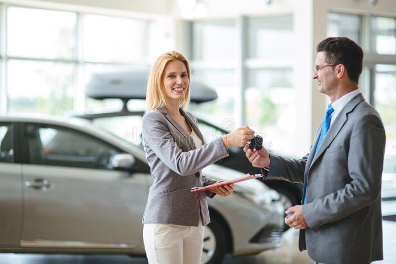 Consultor femenino joven de las ventas del coche que trabaja en la sala de exposici?n foto de archivo