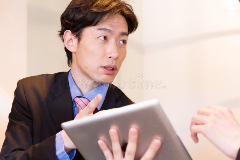 Consultor japonés que habla con el cliente, mostrando datos con el dispositivo de la tableta imagen de archivo libre de regalías