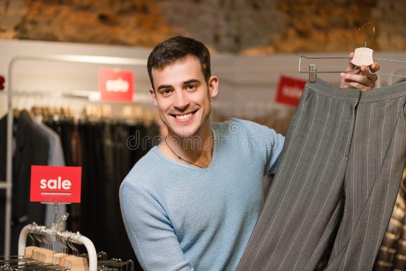 Consultor masculino de las ventas con los pantalones femeninos en tienda fotos de archivo