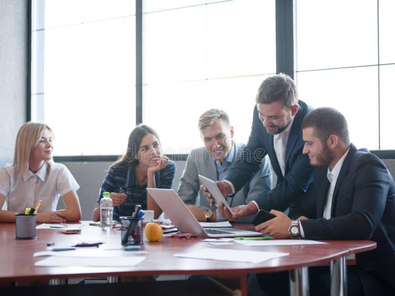 Consultores de negocio que trabajan en un equipo Un grupo de trabajadores jovenes en una reunión en la sala de conferencias de la fotografía de archivo libre de regalías