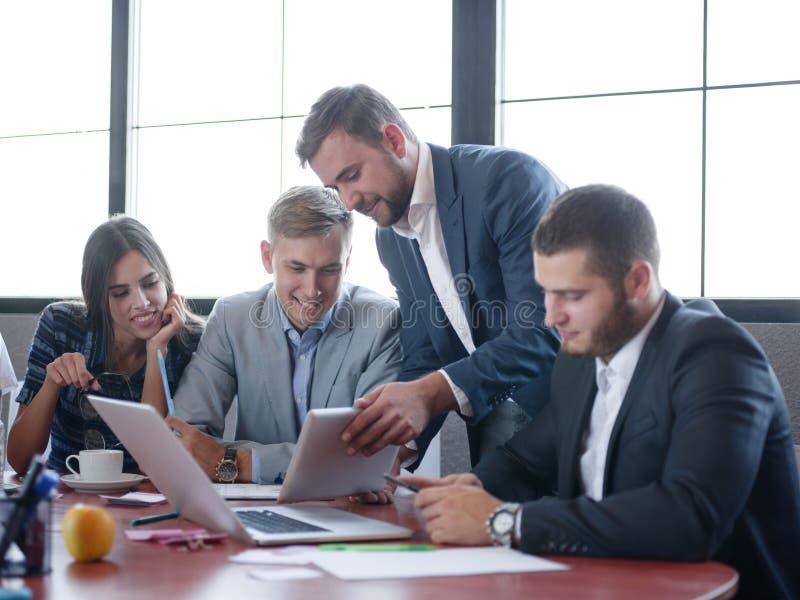 Consultores empresariais ao trabalhar em uma equipe Um grupo de trabalhadores novos em uma reunião na sala de conferências da emp foto de stock royalty free
