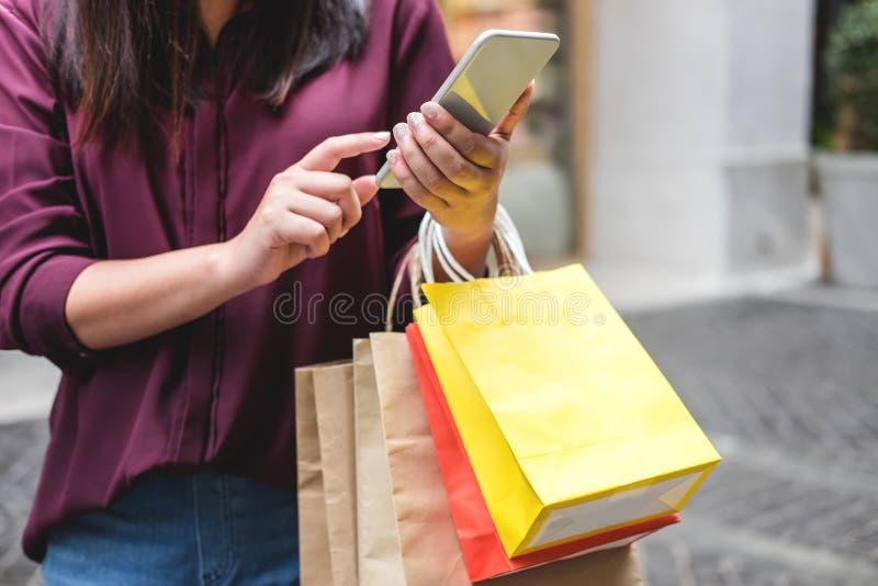 Consumentisme, winkelen, levensstijlconcept, Jonge vrouw kleurrijke het winkelen zakken houden en smartphone die in het winkelen  stock afbeeldingen