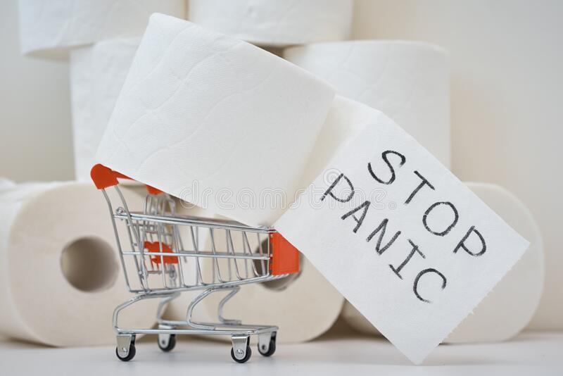 Consumer buying panic about coronavirus covid-19 concept. Toilet paper roll in shopping trolley with inscription stop panic. royalty free stock images