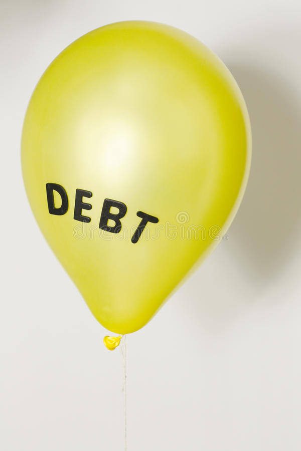 Consumer, government and financial debt bubble. Yellow balloon with the word 'debt' representing the economic, financial and consumer debt bubble stock images