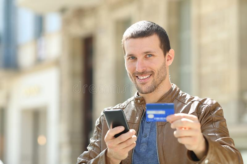 Consumer holding phone and credit card looks at you. Consumer holding mobile phone and credit card looks at you in the street royalty free stock image