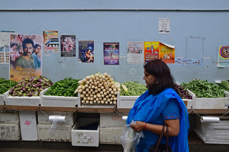 A consumer purchasing fresh produce passing by a long table full of vegetables. In polystyrene boxes. The female buyer is holding a transparent plastic bag with royalty free stock image