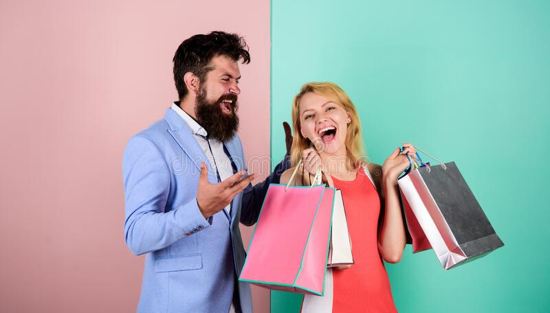 Consumerism addictive behavior. Couple in mall. Shopaholic girlfriend. Black friday concept. Woman on shopping tour. Man. Girl with paper bags. Addicted royalty free stock photos