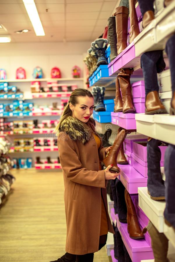 Consumerism, Christmas, shopping, lifestyle concept - young women shopping at shoes store. stock photo
