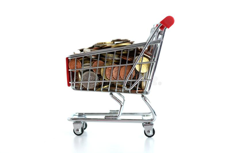 Consumerism concept with shopping trolley full of coins on white background. Consumerism concept with shopping cart full of coins on white background stock photo