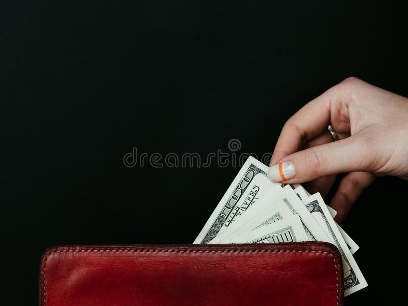 Consumerism money spending dollar banknote wallet. Consumerism and money spending or wasting. personal finances and expenses. woman taking out dollar banknotes royalty free stock photo
