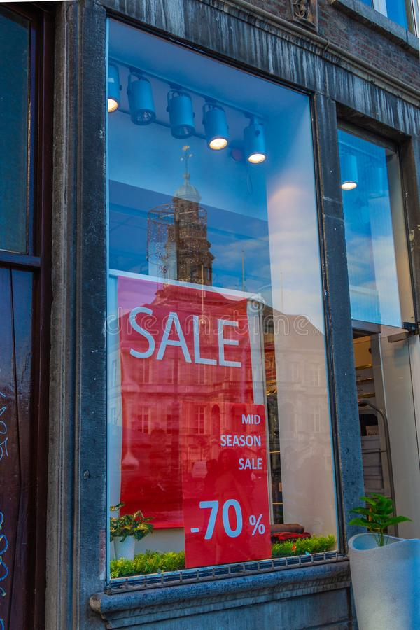Consumerism and sale in downtown in Maastricht with a reflection of the city hall stock photography