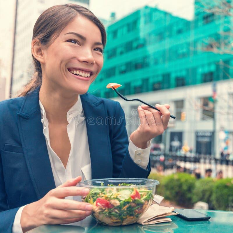 Consumición asiática de la mujer de negocios sana en el trabajo imagen de archivo