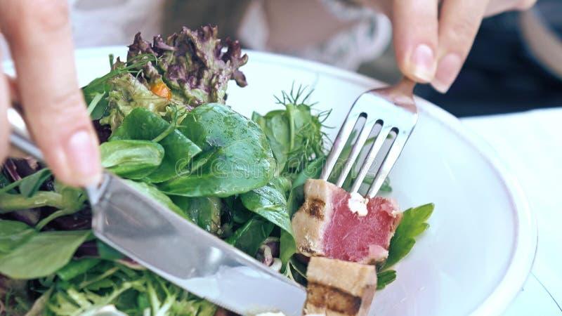 Consumición de la ensalada de Nicoise del atún y de la lechuga en el restaurante, cocina haute imagen de archivo