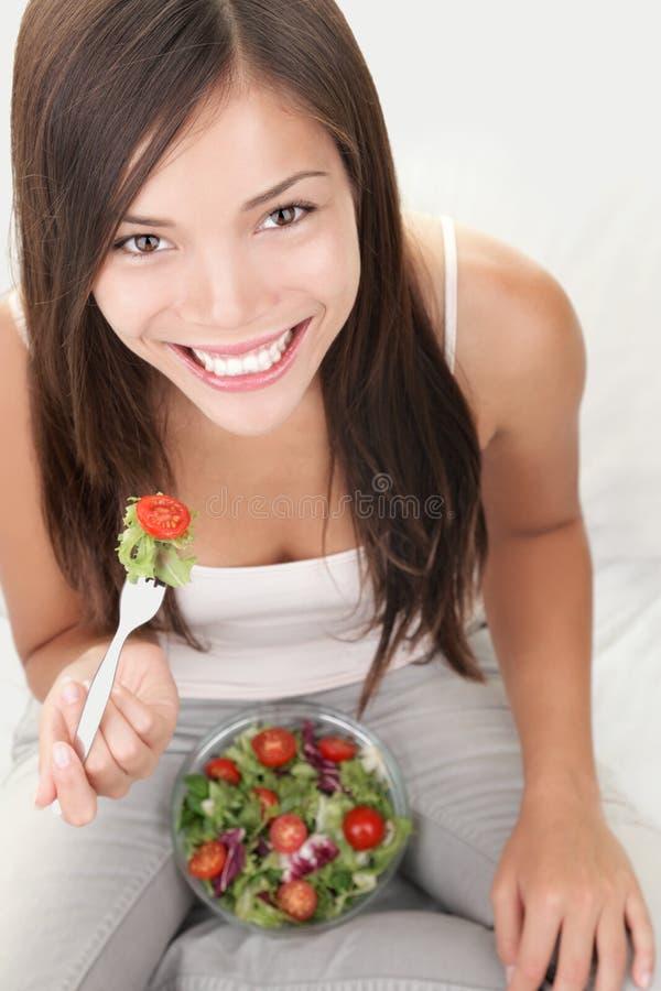Consumición de la mujer de la ensalada sana fotos de archivo