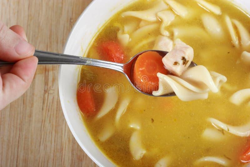 Consumición de la sopa de tallarines del pollo foto de archivo
