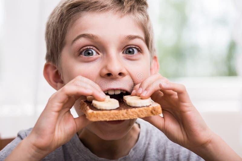 Consumición de la tostada con el chocolate imagen de archivo