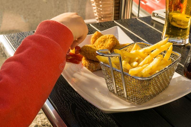 Consumición de las patatas fritas en un comensal foto de archivo