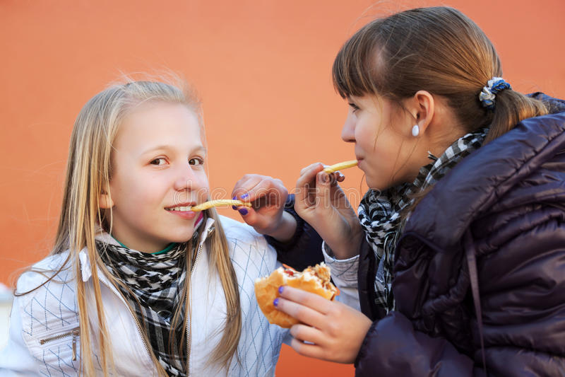 Consumición de los adolescentes hamburguesas imagen de archivo libre de regalías