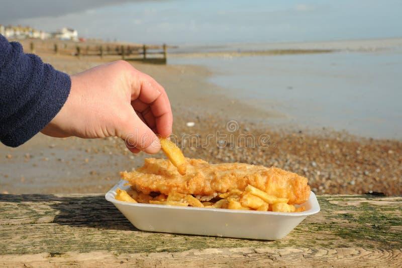 Consumición de pescado frito con patatas fritas fotos de archivo