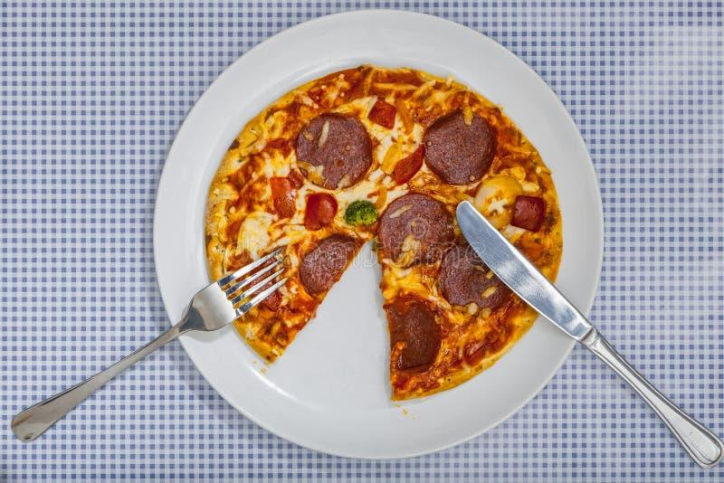 Consumición de un salami de la pizza, opinión de alto ángulo foto de archivo