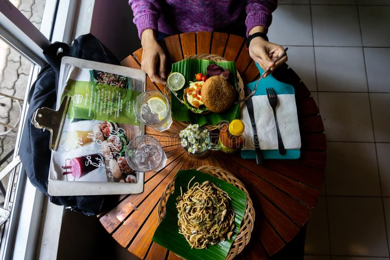 Consumici?n de una comida sana org?nica en la mesa redonda de madera Hay espaguetis con la pimienta negra que sirve en la hoja ve foto de archivo libre de regalías