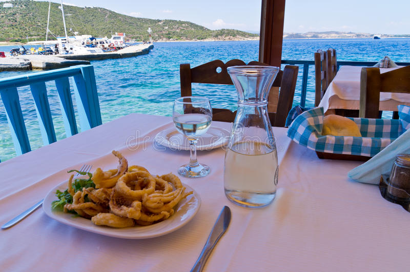 Consumición del calamar frito y consumición del vino blanco en una sombra de un taverna griego típico fotografía de archivo libre de regalías