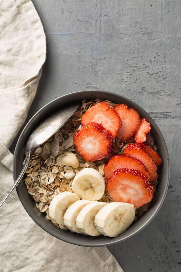 Consumición del cuenco sano del desayuno Muesli y frutas frescas en cuenco de cerámica Consumición limpia, adietando, detox, conc imagen de archivo libre de regalías