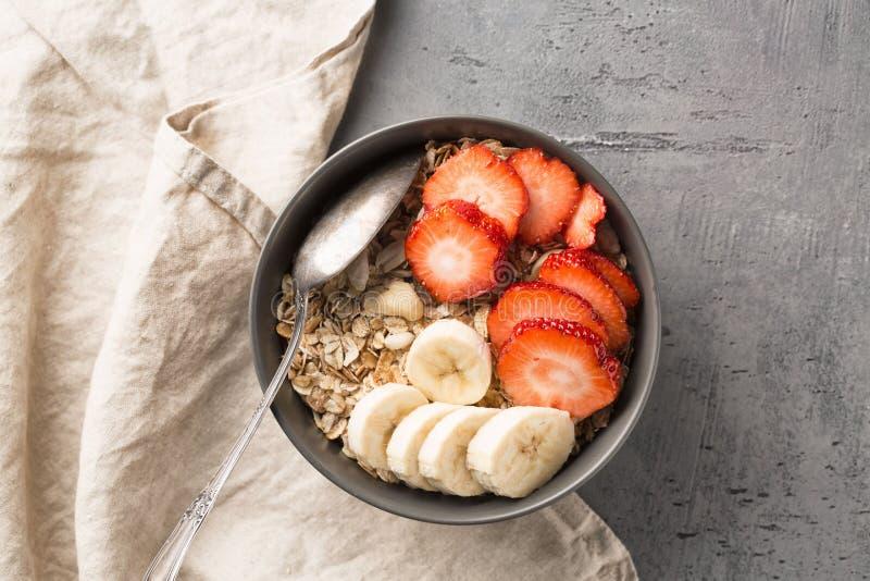Consumición del cuenco sano del desayuno Muesli y frutas frescas en cuenco de cerámica Consumición limpia, adietando, detox, conc fotografía de archivo libre de regalías
