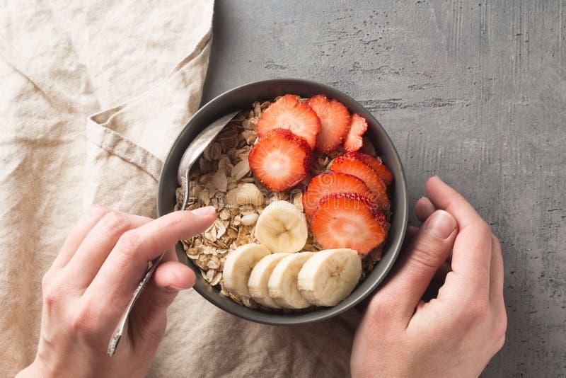 Consumición del cuenco sano del desayuno Muesli y frutas frescas en cuenco de cerámica en manos del ` s de la mujer Consumición l foto de archivo