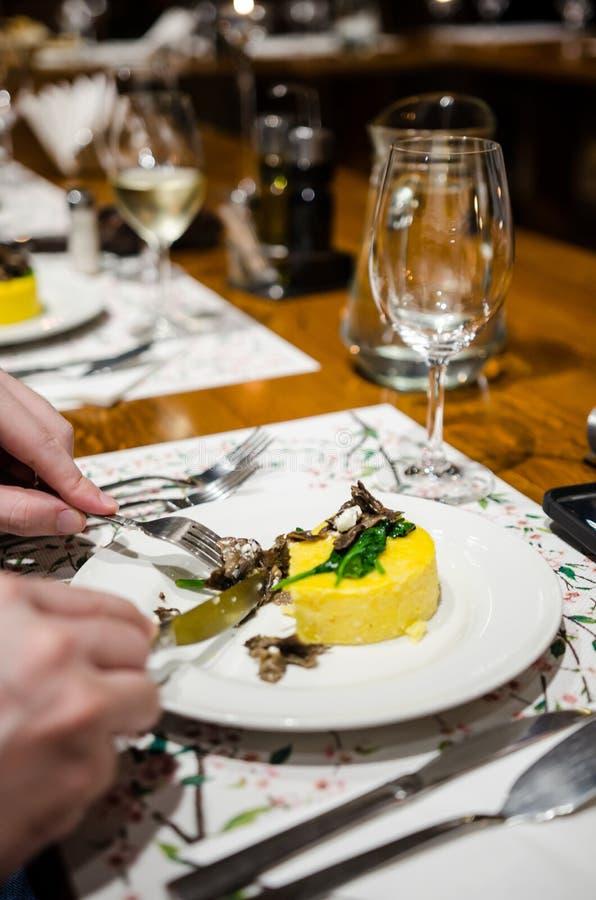 Consumición del Polenta con el hongo y la espinaca de miel imagen de archivo libre de regalías