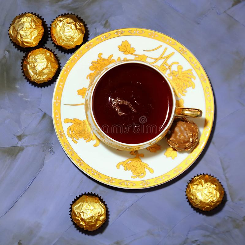 Consumición del té Taza de la porcelana con el caramelo de chocolate del té y del postre imagen de archivo