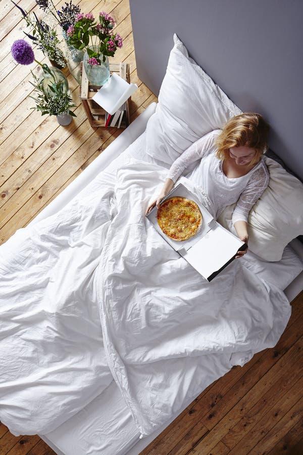 Consumición en pizza en cama foto de archivo libre de regalías