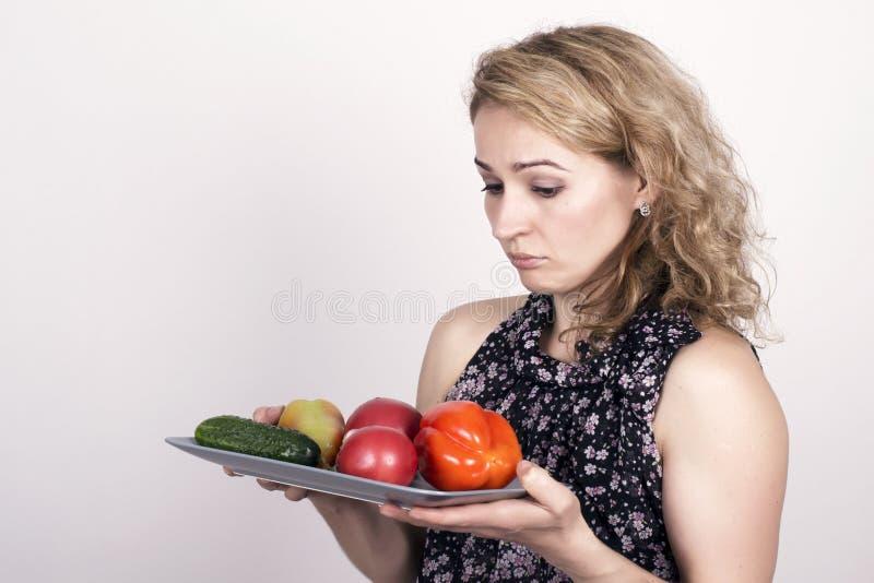 Consumición hermosa de la mujer joven verduras sostener una placa con las verduras, pimienta roja, tomate, pepino Alimento sano fotos de archivo