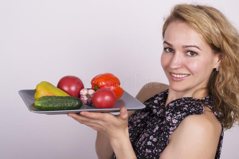 Consumición hermosa de la mujer joven verduras sostener una placa con las verduras, pimienta roja, tomate, pepino Alimento sano imágenes de archivo libres de regalías