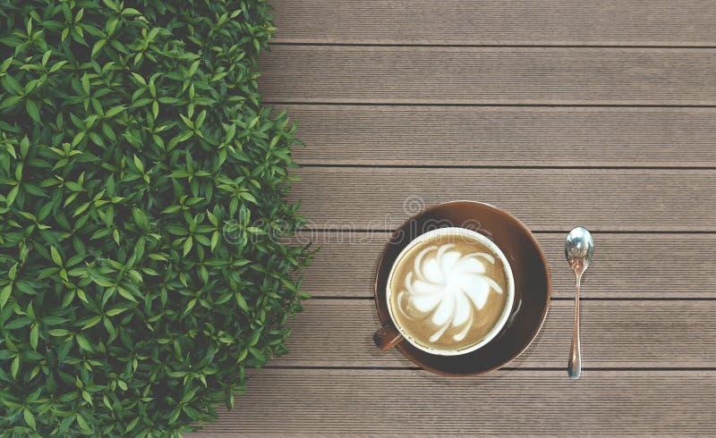 Consumición sabrosa, una taza de café del capuchino adornada con leche del estampado de plores adelante en taza de cerámica marró imagen de archivo