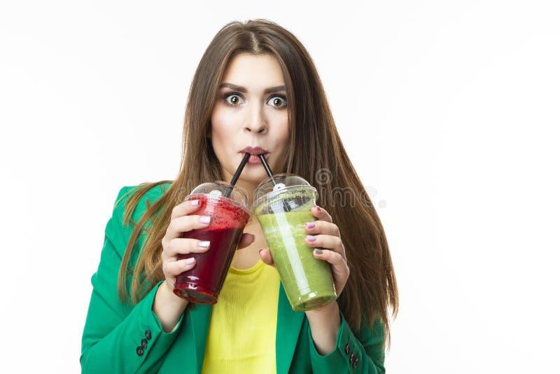 Consumición sana de la comida Mujer sonriente que bebe el Smoothie vegetal del Detox verde y rojo Presentación en chaqueta verde  fotos de archivo libres de regalías