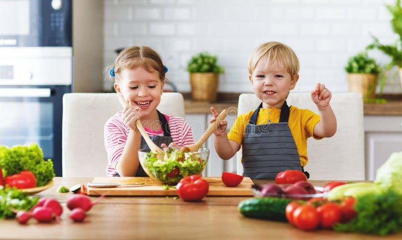 Consumición sana Los niños felices preparan la ensalada vegetal en kitc foto de archivo