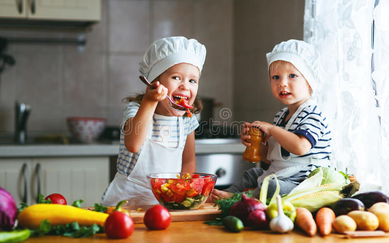Consumición sana Los niños felices preparan la ensalada vegetal en kitc imágenes de archivo libres de regalías
