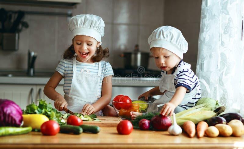 Consumición sana Los niños felices preparan la ensalada vegetal en kitc fotos de archivo