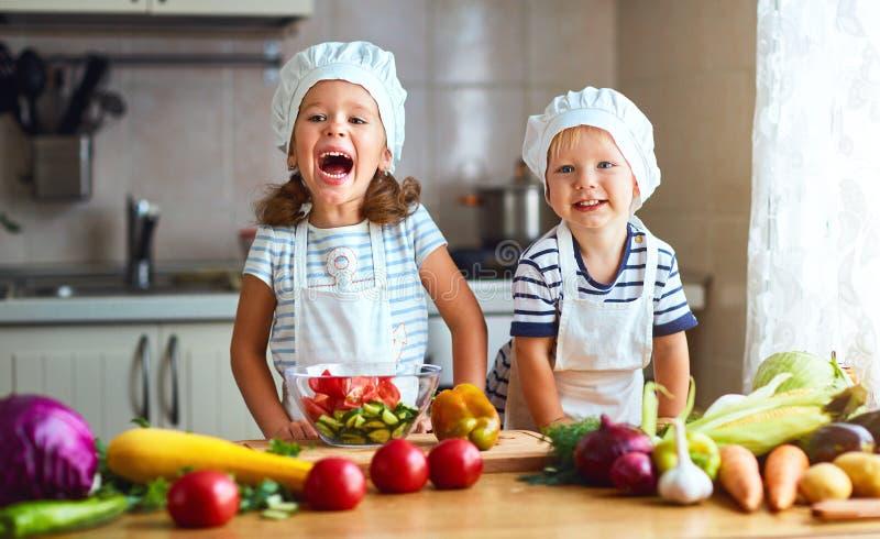 Consumición sana Los niños felices preparan la ensalada vegetal en kitc imagenes de archivo
