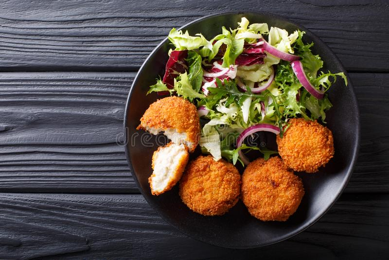 Consumición sana: Torta del bacalao de los pescados y primer fresco de la ensalada en un plat imagen de archivo libre de regalías