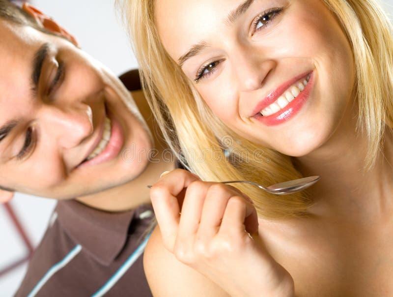 Consumición sonriente joven de los pares fotografía de archivo libre de regalías