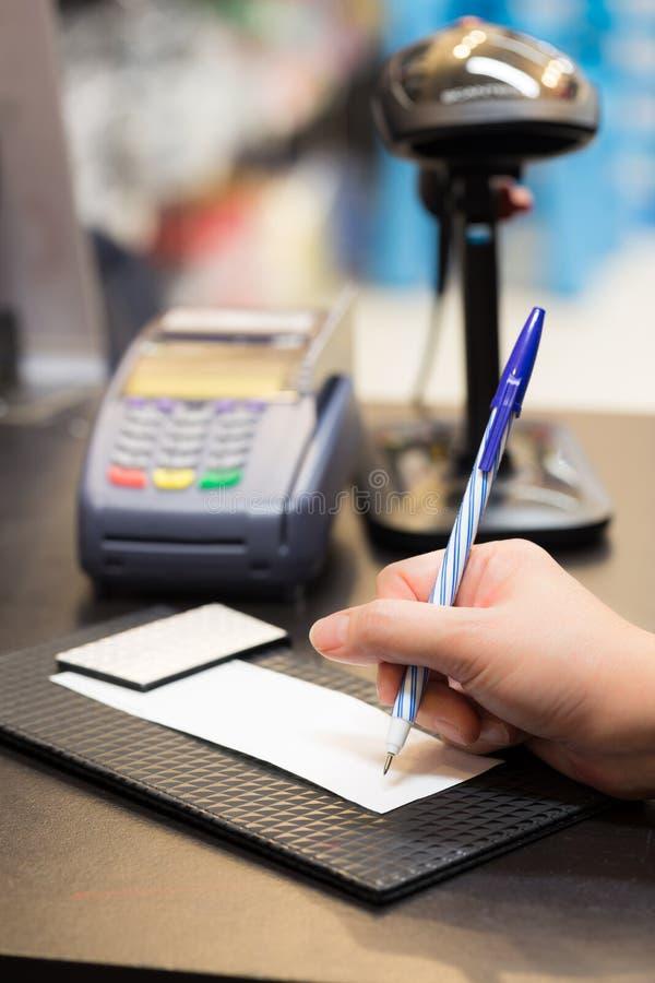 Consumidor que firma en un recibo de la transacción de venta imagenes de archivo