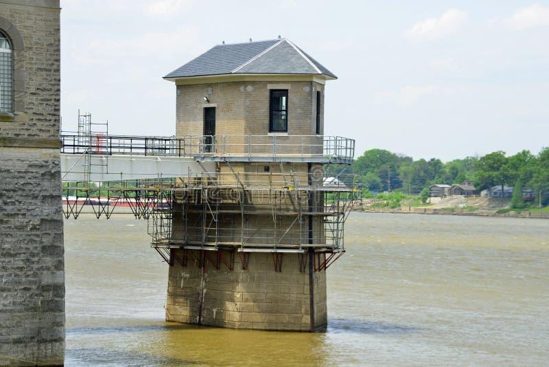Consumo de agua en el edificio de la central depuradora bajo restauración en el borde del río fotos de archivo
