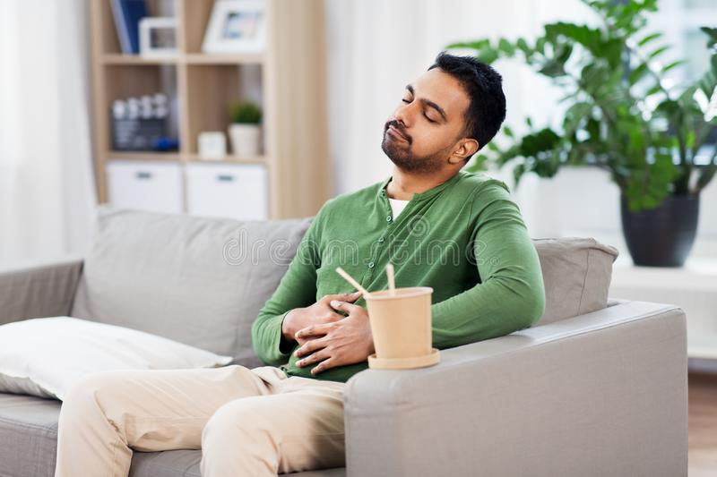 Pleased indian man eating takeaway food at home. Consumption and people concept - full and pleased indian man eating takeaway food at home stock image
