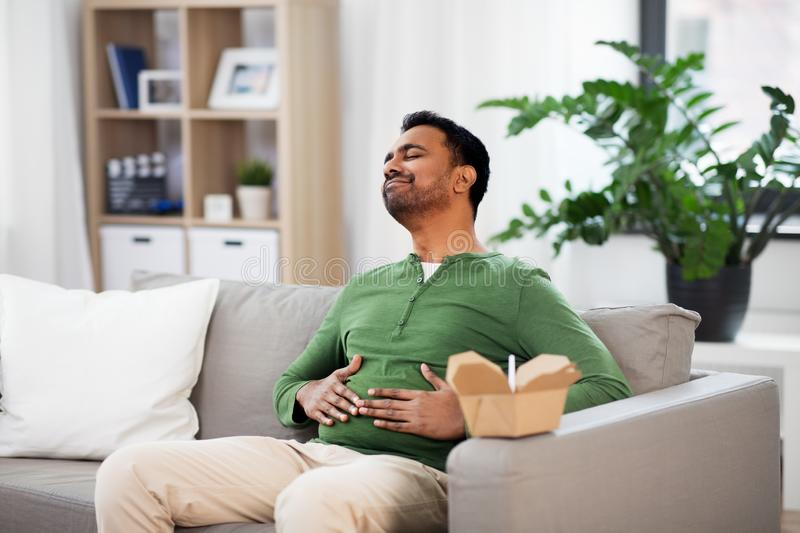 Pleased indian man eating takeaway food at home. Consumption and people concept - full and pleased indian man eating takeaway food at home royalty free stock images