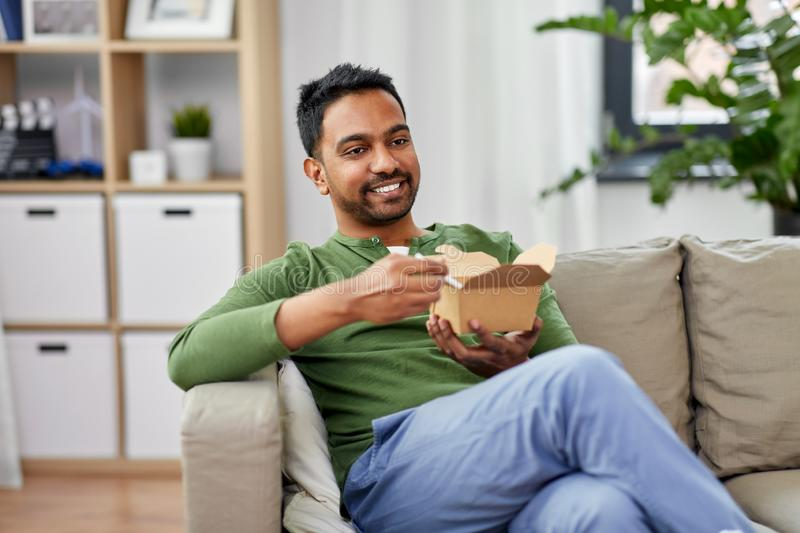 Smiling indian man eating takeaway food at home. Consumption and people concept - smiling indian man eating takeaway food at home stock image